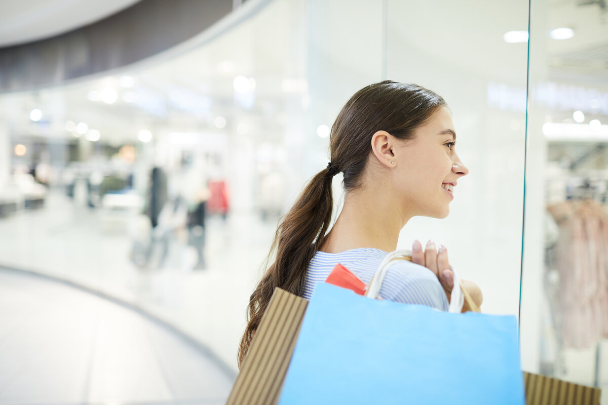 brand personality - Pretty customer with bags standing by shop window and looking at new fashion collection in one of departments