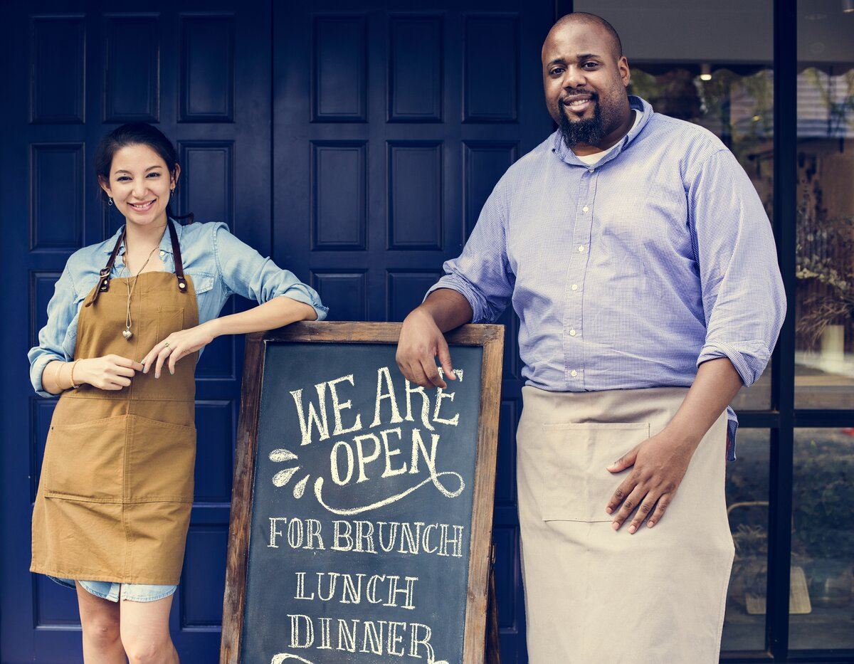 cheerful owners standing with open sign business success after covid