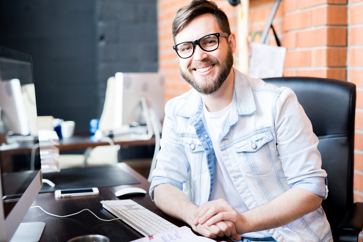 reviews business manager wearing casual clothes smiling happily at camera while sitting at computer desk