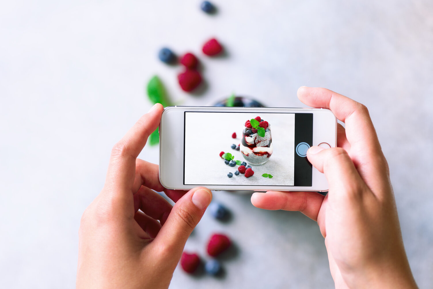 Girl taking photos of breakfast, chia pudding with berries to mobile phone for Social Media