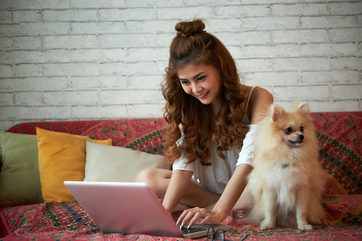 A woman with laptop and a dog